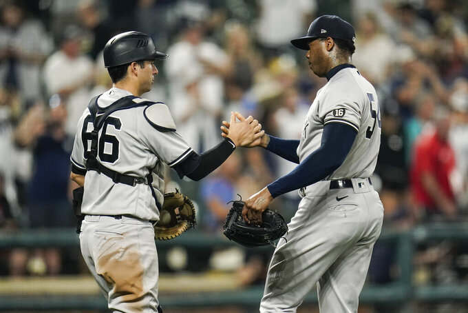 New York Yankees catcher Kyle Higashioka (66) and relief pitcher Aroldis Chapman react after defeating the Baltimore Orioles 7-2 during a baseball game, Tuesday, Sept. 14, 2021, in Baltimore. (AP Photo/Julio Cortez)