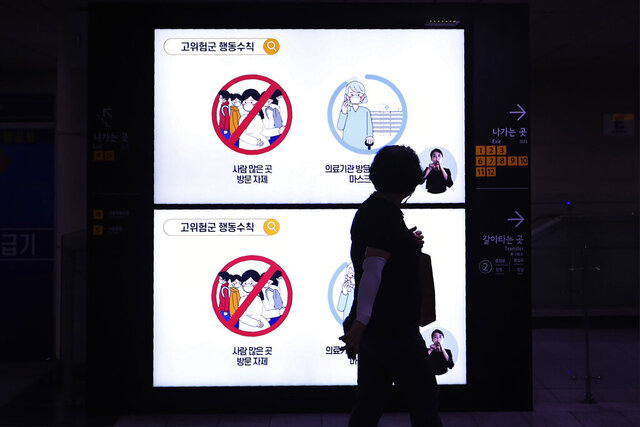 A woman wearing a mask passes screens showing social behavior rules to help curb the spread of the coronavirus at a subway station in Seoul, South Korea, Thursday, Aug. 27, 2020. South Korea has added nearly 4,000 infections to its caseload while reporting triple-digit daily jumps in each of the past 14 days, prompting health experts to warn about hospitals possibly running out of capacity. The sign reads: