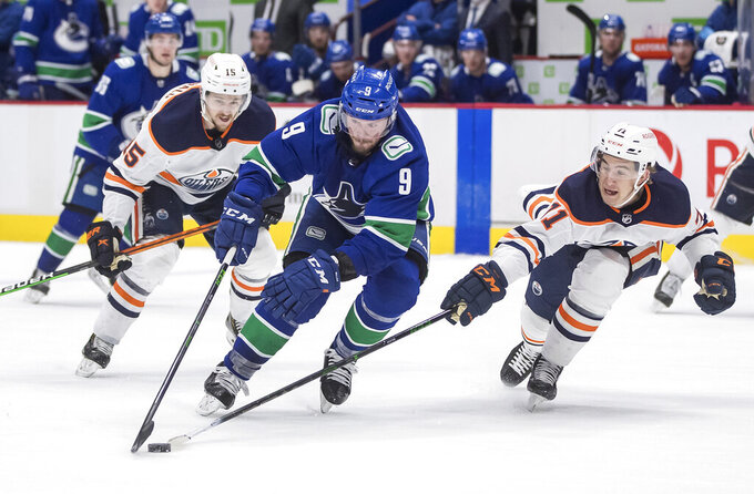 Vancouver Canucks' J.T. Miller (9) skates around Edmonton Oilers' Ryan McLeod (71) and scores a goal during the second period of an NHL hockey game, Monday, May 3, 2021, in Vancouver, British Columbia. (Darryl Dyck/The Canadian Press via AP)