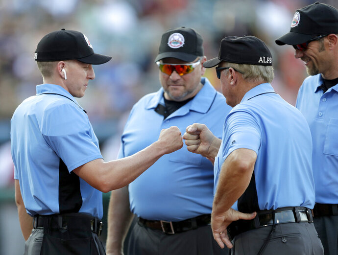 FILE - In this July 10, 2019, file photo, home plate umpire Brian deBrauwere, left, huddles with officials while wearing an earpiece connected to a ball and strikes calling system before the Atlantic League All-Star minor league baseball game in York, Pa. DeBrauwere wore the earpiece connected to an iPhone in his ball bag which relayed ball and strike calls upon receiving it from a TrackMan computer system that uses Doppler radar. The independent Atlantic League became the first American professional baseball league to let the computer call balls and strikes during the all star game. Umpires agreed to cooperate with Major League Baseball in the development and testing of an automated ball-strike system as part of a five-year labor contract announced Saturday, Dec. 21, two people familiar with the deal told The Associated Press. The Major League Baseball Umpires Association also agreed to cooperate and assist if Commissioner Rob Manfred decides to utilize the system
