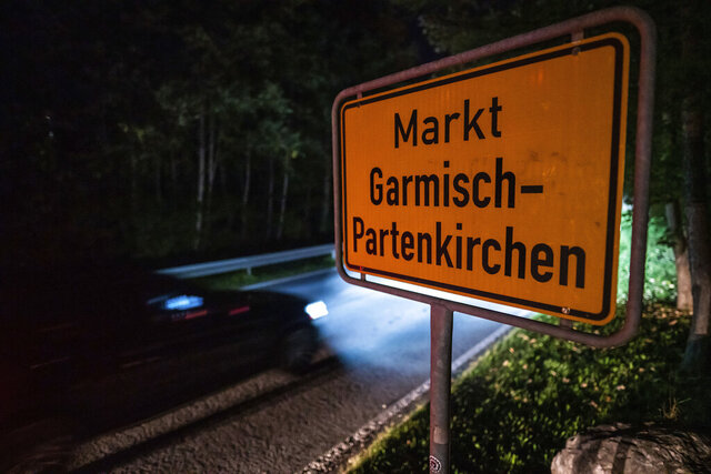 FILE-In this Sept. 13, 2020 taken photo a car drives past the place name sign in Garmisch-Partenkirchen, Germany. Officials in southern Germany are considering imposing hefty fines against a 26-year-old American woman linked to a cluster of coronavirus cases in the Alpine resort town of Garmisch-Partenkirchen, including at a hotel that caters to U.S. military personnel. (Lino Mirgeler/dpa via AP)
