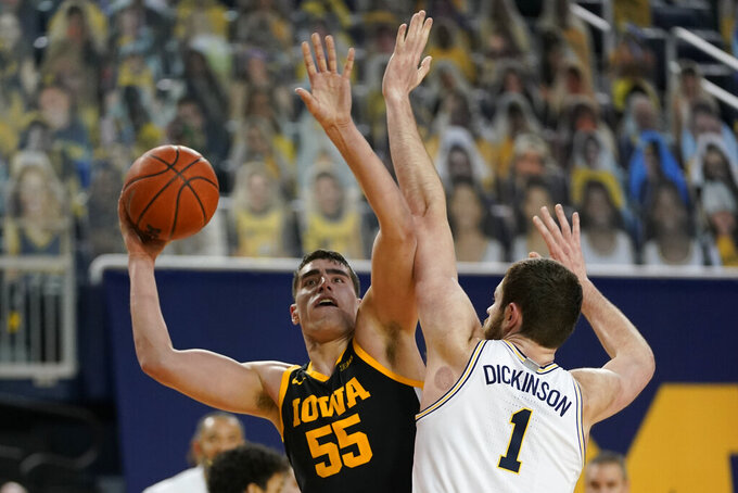 Iowa center Luka Garza (55) is defended by Michigan center Hunter Dickinson (1) during the first half of an NCAA college basketball game, Thursday, Feb. 25, 2021, in Ann Arbor, Mich. (AP Photo/Carlos Osorio)