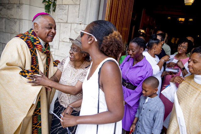FILE - In this Sunday, June 2, 2019, file photo, Washington D.C. Archbishop Wilton Gregory, left, greets parishioners following Mass at St. Augustine Church in Washington. Pope Francis has  named 13 new cardinals, including Washington D.C. Archbishop Wilton Gregory, who would become the first Black U.S. prelate to earn the coveted red cap.  In a surprise announcement from his studio window to faithful standing below in St. Peter's Square, Sunday, Oct. 25, 2020, Francis said the churchmen would be elevated to a cardinal's rank in a ceremony on Nov. 28. (AP Photo/Andrew Harnik, File)
