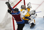 Nashville Predators goaltender Pekka Rinne, back, drops to the ice after missing a shot off the stick of Colorado Avalanche left wing Blake Comeau for a goal in the first period of Game 3 of an NHL hockey first-round playoff series Monday, April 16, 2018, in Denver. (AP Photo/David Zalubowski)