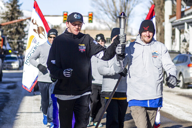 In this Feb. 4, 2020 photo Special Olympics athletes Brendan Burke and Gary Endecott carry the torch as they lead fellow athletes and and supporters down South Cache Street during the Law Enforcement Torch Run in Jackson, Wyo. The Special Olympics Wyoming Winter Games begin the next morning and ran through early Thursday afternoon with alpine skiing and snowboarding at Jackson Hole Mountain Resort and cross country skiing and snowshoeing at the town's high school athletic fields. (Ryan Dorgan/Jackson Hole News & Guide via AP)