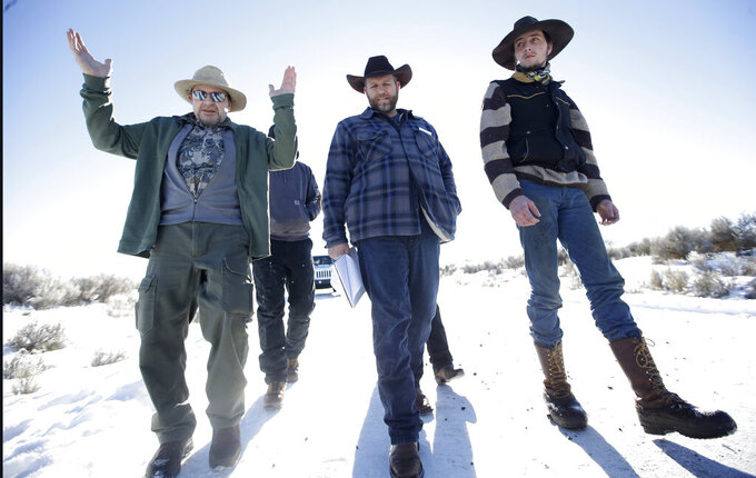 FILE - In this Jan 8, 2016, file photo, Burns resident Steve Atkins, left, talks with Ammon Bundy, center, one of the sons of Nevada rancher Cliven Bundy, following a news conference at Malheur National Wildlife Refuge near Burns, Ore. Cliven and his sons Ryan and Ammon have engaged in armed standoffs with the federal government, first in a fight over grazing permits on federal land in Nevada in 2014, and then in a 40-day occupation of the Malheur Wildlife Refuge in Oregon in 2016. Those standoffs drew the sympathies of some Western ranchers and farmers who feared they were losing the ability to prosper financially. (AP Photo/Rick Bowmer, File)