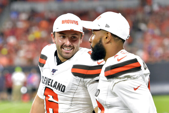 FILE - In this Aug. 8, 2019, file photo, Cleveland Browns' Baker Mayfield, left, smiles as he talks with wide receiver Odell Beckham Jr. during the second half of an NFL preseason football game against the Washington Redskins in Cleveland. Beckham believes the Browns offense will come around. Until then, he's going to defend Mayfield. (AP Photo/David Richard, File)