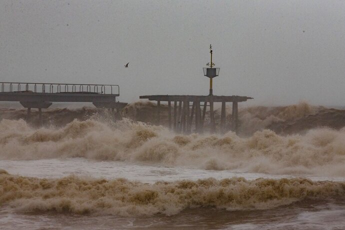 Waves hit a partially damage bridge during a storm in Badalona's beach, outskirts of Barcelona, Spain, Wednesday, Jan. 22, 2020. Massive waves and gale-force winds smashed into seafront towns, damaging many shops and restaurants and flooding some streets. (AP Photo/Joan Mateu)