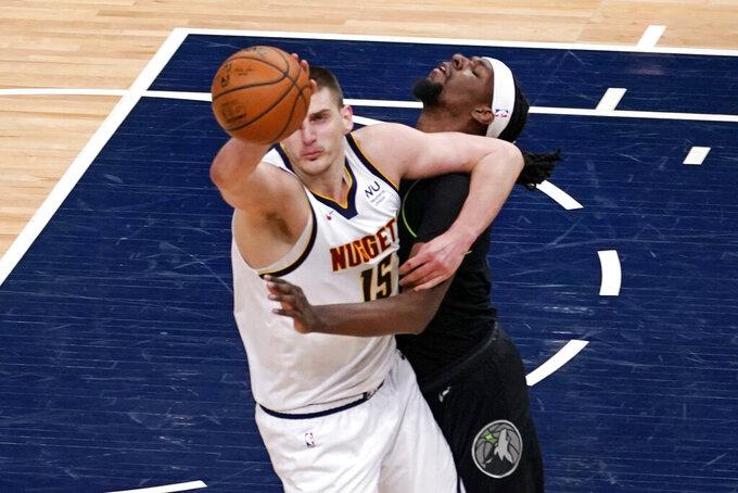 Denver Nuggets' Nikola Jokic (15) and Minnesota Timberwolves' Naz Reid collide during the first half of an NBA basketball game Thursday, May 13, 2021, in Minneapolis. (AP Photo/Jim Mone)