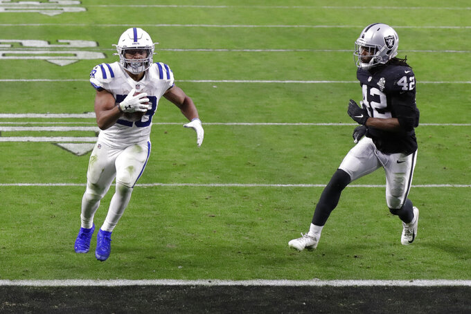 Indianapolis Colts running back Jonathan Taylor (28) runs in for a touchdown against Las Vegas Raiders outside linebacker Cory Littleton (42) during the second half of an NFL football game, Sunday, Dec. 13, 2020, in Las Vegas. (AP Photo/Isaac Brekken)