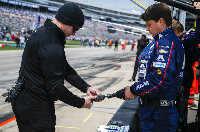 A member of Hendrick Motorsports, left, checks the performance of their impact air wrench before a NASCAR Cup auto race at Texas Motor Speedway, Sunday, March 31, 2019, in Fort Worth, Texas. (AP Photo/Brandon Wade)