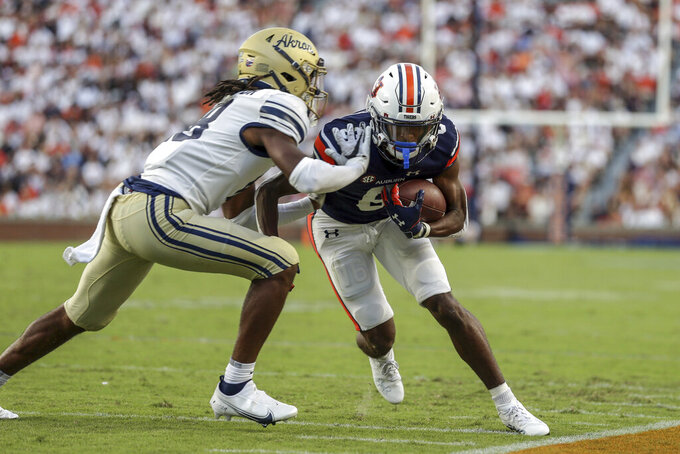 Auburn wide receiver Ja'Varrius Johnson (6) is shoved out of bounds by Akron cornerback A.J. Watts (18) during the first half of an NCAA college football game Saturday, Sept. 4, 2021, in Auburn, Ala. (AP Photo/Butch Dill)