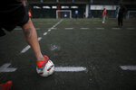 A player steps on the ball during an amateur soccer match at a local club, Play Futbol 5, in Pergamino, Argentina, Wednesday, July 1, 2020. In order to continue playing amid government restrictions to curb the spread of the new coronavirus, the club divided its soccer field into 12 rectangles to mark limited areas for each player, keeping them from making physical contact. (AP Photo/Natacha Pisarenko)