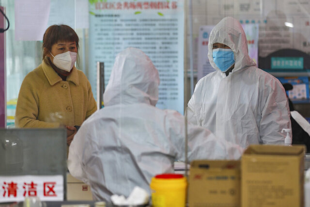 Medical workers in protective gear talk with a woman suspected of being ill with a coronavirus at a community health station in Wuhan in central China's Hubei Province, Monday, Jan. 27, 2020. China on Monday expanded sweeping efforts to contain a viral disease by extending the Lunar New Year holiday to keep the public at home and avoid spreading infection. (Chinatopix via AP)