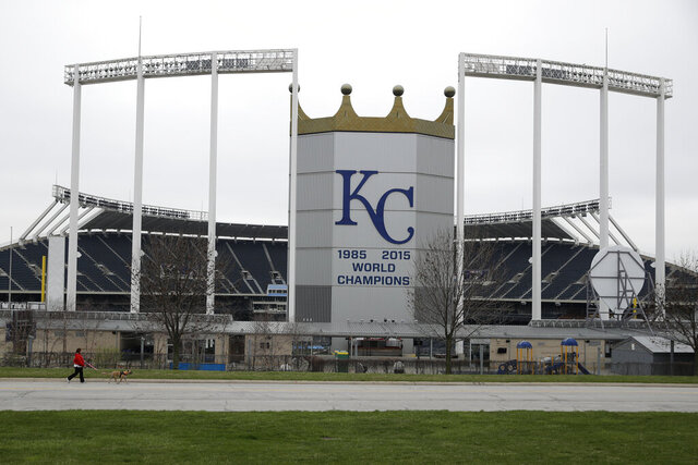 A woman and her dog walk past Kauffman Stadium, home of the Kansas City Royals baseball team, Wednesday, March 25, 2020, in Kansas City, Mo. The start of the regular season, which was set to start on Thursday, is on hold indefinitely because of the coronavirus pandemic. (AP Photo/Charlie Riedel)