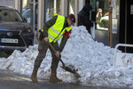 A military police officer clears snow and ice from the street in Madrid, Spain, Tuesday, Jan. 12, 2021. Spain is grappling to return normality after the largest snowfall in half a century but record-low temperatures have formed ice that are sending many citizens to already strained hospital emergency rooms. Schools remain closed in Madrid and many other parts of central Spain, with authorities focusing on reopening roads and stocking up supermarkets. (AP Photo/Paul White)