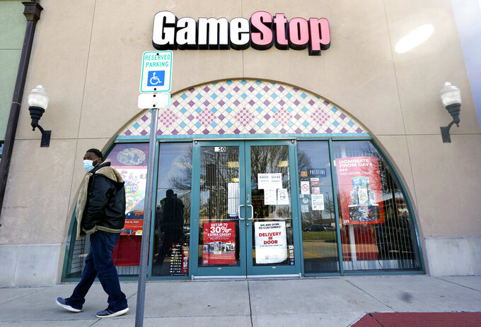 FILE - In this Jan. 28, 2021 file photo, a pedestrian passes a GameStop storefront in Dallas. A hefty tax benefit helped drive GameStop's fiscal fourth-quarter profit sharply higher, but the video-game retailer's sales declined despite a surge in its online business. The company's latest results fell short of Wall Street's expectations. (AP Photo/LM Otero, File)