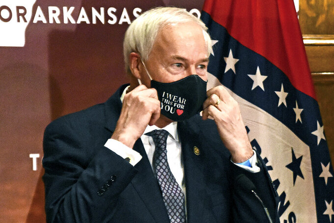 FILE - In this July 20, 2020 file photo, Arkansas Gov. Asa Hutchinson removes his mask before a briefing at the state capitol in Little Rock. Hutchinson has signed into law a measure that would allow doctors to refuse to treat someone because of moral or religious objections. Gov. Hutchinson on Friday, March 26, 2021, signed the legislation, despite objections that it would give medical providers broad powers to turn away LGBTQ patients and others. (Staci Vandagriff/The Arkansas Democrat-Gazette via AP, File)