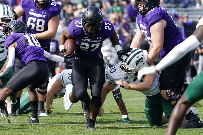 Northwestern running back Anthony Tyus III (27) runs with the ball past Ohio linebacker Cannon Blauser during the second half of an NCAA college football game in Evanston, Ill., Saturday, Sept. 25, 2021. Northwestern won 35-6. (AP Photo/Nam Y. Huh)