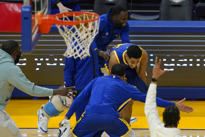 Golden State Warriors guard Jordan Poole, middle, celebrates with teammates after shooting a three-point basket at the third period buzzer during an NBA basketball game against the Utah Jazz in San Francisco, Monday, May 10, 2021. (AP Photo/Jeff Chiu)
