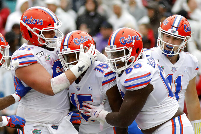 Florida's Jacob Copeland (15) is congratulated by teammates after scoring a touchdown against South Carolina in the first half of an NCAA college football game Saturday, Oct. 19, 2019, in Columbia, SC. (AP Photo/Mic Smith)