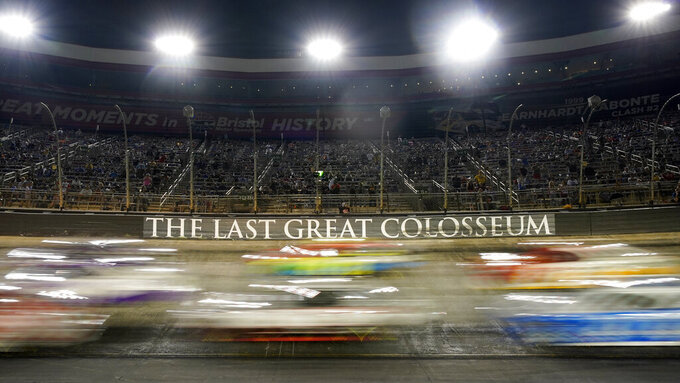 Cars come through a turn during a NASCAR Cup Series auto race at Bristol Motor Speedway Saturday, Sept. 18, 2021, in Bristol, Tenn. (AP Photo/Mark Humphrey)