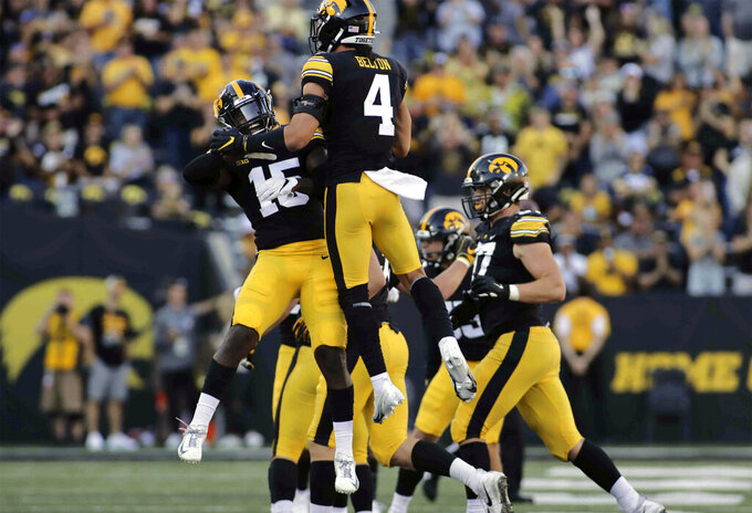 Iowa defensive back Dallas Craddieth (15) and teammate defensive back Dane Belton (4) celebrate a defensive stop during the second half of an NCAA college football game against Colorado State, Saturday, Sept. 25, 2021, in Iowa City, Iowa. (AP Photo/Ron Johnson)