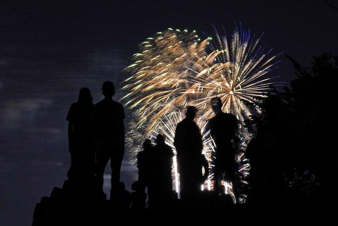 People are silhouetted against fireworks as they watch a Fourth of July celebration from a park in Kansas City, Mo., Saturday, July 3, 2021. (AP Photo/Charlie Riedel)