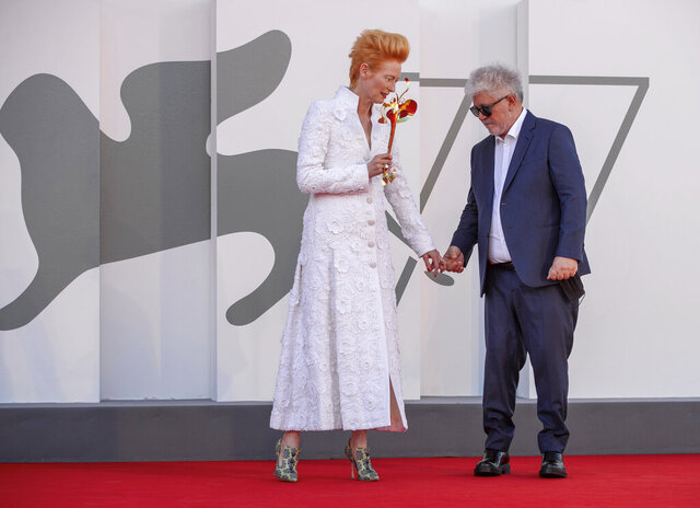Director Pedro Almodovar, right, and actress Tilda Swinton pose on the red carpet of the movie 'The human voice' during the 77th edition of the Venice Film Festival at the Venice Lido, Italy, Thursday, Sep. 3, 2020. The Venice Film Festival goes from Sept. 2 through Sept. 12. Italy was among the countries hardest hit by the coronavirus pandemic, and the festival will serve as a celebration of its re-opening and a sign that the film world, largely on pause since March, is coming back as well. (AP Photo/Domenico Stinellis)