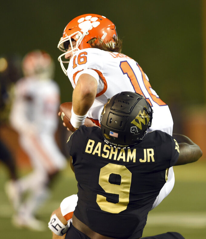 Wake Forest defensive end Carlos Basham Jr. sacks Clemson quarterback Trevor Lawrence in the first half of an NCAA college football game Saturday, Sept. 12, 2020, in Winston-Salem, N.C. (Walt Unks/The Winston-Salem Journal via AP)