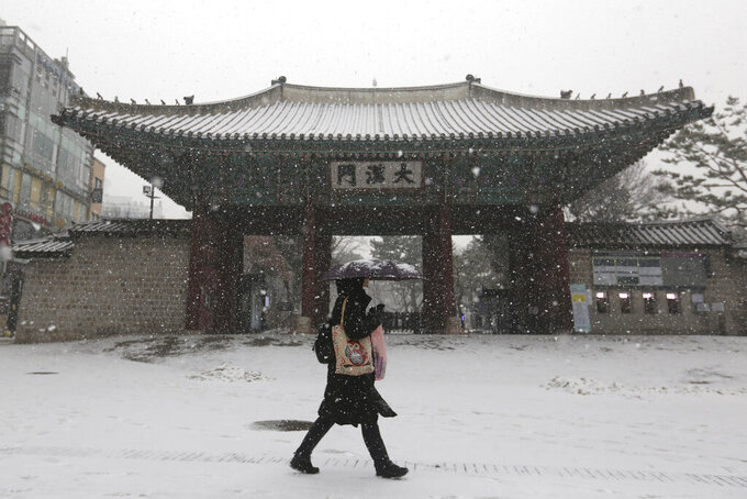 A woman wearing a face mask as a precaution against the coronavirus passes by the main gate of the Deoksu Palace in the snow in Seoul, South Korea, Tuesday, Jan. 12, 2021. (AP Photo/Ahn Young-joon)