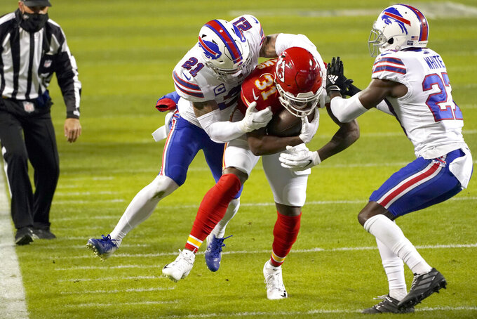Kansas City Chiefs running back Darrel Williams (31) is tackled by Buffalo Bills safety Jordan Poyer (21) and cornerback Tre'Davious White, right, during the first half of the AFC championship NFL football game, Sunday, Jan. 24, 2021, in Kansas City, Mo. (AP Photo/Charlie Riedel)