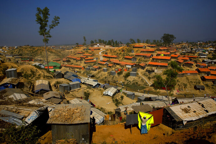 FILE - In this Jan. 23, 2018 file photo, a Rohingya refugee hangs a blanket out to dry at Balukhali refugee camp, about 50 kilometers (32 miles) from Cox's Bazar, Bangladesh. Authorities in Bangladesh said Tuesday, Oct. 22, 2019, that they want to start relocating thousands of Rohingya refugees to a Bay of Bengal island soon from crammed camps near the border with Myanmar, from where they fled. Top government administrator in Cox's Bazar, Kamal Hossain, said they listed 100 families willing to move to Bhasan Char, an island hours by boat from the mainland. The government has said it will relocate 100,000 refugees to the island in phases. (AP Photo/Manish Swarup, File)