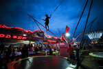 In this picture taken Saturday, Sept. 14, 2019, a child jumps on a trampoline at an autumn fair in Titu, southern Romania. Romania's autumn fairs are a loud and colorful reminder that summer has come to an end and, for many families in poorer areas of the country, one of the few affordable public entertainment events of the year. (AP Photo/Vadim Ghirda)