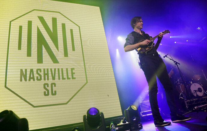 A band performs as the logo of the Nashville Soccer Club is displayed at the unveiling of the MLS team's name, logo and colors Wednesday, Feb. 20, 2019, in Nashville, Tenn. The expansion franchise is due to start play in 2020. (AP Photo/Mark Humphrey)