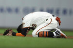 San Francisco Giants' Mauricio Dubon kneels on the field after colliding with Colorado Rockies' Tony Wolters during the seventh inning of a baseball game Wednesday, Sept. 25, 2019, in San Francisco. (AP Photo/Ben Margot)