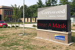 A sign outside of Greenwood Elementary School promotes mask-wearing on Thursday, Sept. 17, 2020, in Des Moines, Iowa. A dispute between Iowa's governor and the state's largest school district could mean summer school for students and crippling bills for the school system. Des Moines school officials have repeatedly refused to abide by Republican Gov. Kim Reynolds' order that districts hold at least half their classes in-person, saying it's not safe. (AP Photo/Scott McFetridge)