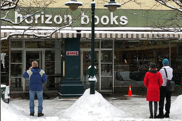 People gaze into Horizon Books Monday, Jan. 13, 2019, in Traverse City, Mich. The bookstore that has served Traverse City for nearly 60 years is closing. Horizon Books has been a downtown landmark on Front Street, selling books and making space for musicians, authors and community groups. The store will close at some point this year. (AP Photo/John Flesher)