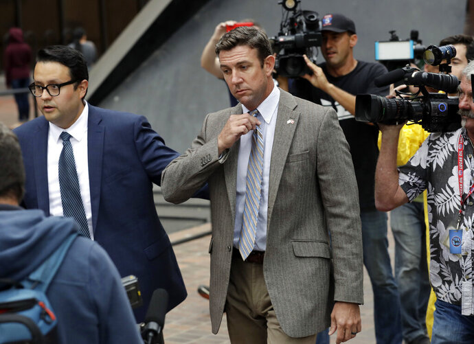 CORRECTS TO ATTRIBUTE THE REFERENCE TO HUNTER, NOT A JUSGE - FILE - In this Sept. 24, 2018, file photo, U.S. Rep. Duncan Hunter, center, leaves court in San Diego. The California Republican plans to plead guilty on Tuesday, Dec. 3, 2019, to the misuse of campaign funds and has indicated he will leave Congress, he told KUSI television in San Diego in an interview that aired Monday. (AP Photo/Gregory Bull, File)