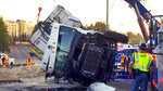 In this Wednesday, May 23, 2018, photo provided by KOMONews.com, a semi-truck that dumped chicken feathers on and alongside Interstate 5 is lifted in Federal Way, Wash. A tractor-trailer made a fowl mess when it rolled over, dumping about 40,000 pounds of chicken feathers across the freeway. Washington State Patrol Trooper Rick Johnson says the driver told investigators he fell asleep at about 3:30 a.m. north of Tacoma and lost control of the truck, which hit a guardrail and overturned. The truck was hauling the feathers from a poultry facility to a rendering company in Vancouver, British Columbia. (Joshua Morgan/KOMONews.com via AP)