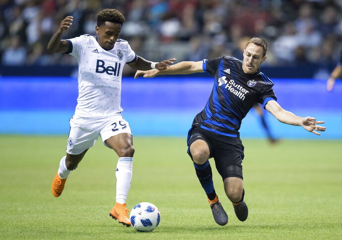 Vancouver Whitecaps' Yordy Reyna, left, beats San Jose Earthquakes' Francois Affolter to the ball and takes a shot on goal during the second half of an MLS soccer match in Vancouver, British Columbia, Wednesday, May 16, 2018. (Darryl Dyck/The Canadian Press via AP)
