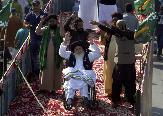 FILE - In this Saturday, Nov. 7, 2020 file photo, Khadim Hussein Rizvi, center on wheelchair, head of 'Tehreek-e-Labaik Pakistan, a religious political party, leads an anti France rally in Karachi, Pakistan. Rizvi, a radical religious cleric, who led tens of thousands in anti-France around the country, died Thursday, Nov. 19, 2020. His spokesman and a doctor at the hospital where Rizvi died said he was suffering from COVID-like symptoms but was not tested for the virus. (AP Photo/Fareed Khan, File)
