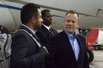 This image released by Netflix shows Kal Penn as Seth Wright, left, and Kiefer Sutherland as Tom Kirkman in