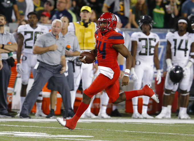 Arizona quarterback Khalil Tate (14) runs for a first down against Oregon in the second half during an NCAA college football game, Saturday, Oct. 27, 2018, in Tucson, Ariz. (AP Photo/Rick Scuteri)