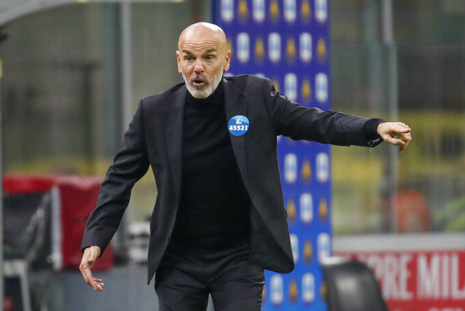 FILE - In this Sunday, Nov. 8, 2020 file photo, AC Milan manager Stefano Pioli calls out to his players during a Serie A soccer match between AC Milan and Hellas Verona, at the San Siro Stadium, in Milan, Italy. AC Milan coach Stefano Pioli has recovered from the coronavirus and will be back on the sidelines for Thursday's Europa League match against Celtic. Milan said on Wednesday, Dec. 2, 2020 that the latest tests carried out on Pioli and his assistant Giacomo Murelli were negative for COVID-19. (AP Photo/Antonio Calanni, File)