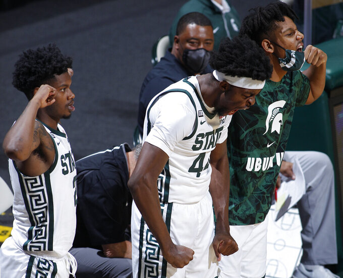Michigan State's Gabe Brown, center, Rocket Watts, left, and A.J. Hoggard cheer on the bench during the second half of an NCAA college basketball game against Western Michigan, Sunday, Dec. 6, 2020, in East Lansing, Mich. (AP Photo/Al Goldis)
