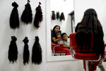 In this April 2, 2019 photo, Nelly Navarro sits with her kids Nerianny and Luis in a beauty salon where she came to consult how much money she could get for her hair, in Caracas, Venezuela. Navarro said she needs the $100 to travel to Colombia where she's planning to move. (AP Photo/Natacha Pisarenko)