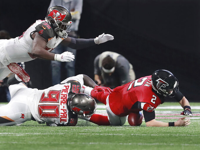 Atlanta Falcons quarterback Matt Ryan, right, fumbles as he is sacked by Tampa Bay Buccaneers linebacker Jason Pierre-Paul, bottom left, during the fourth quarter of an NFL football game Sunday, Nov. 24, 2019, in Atlanta. Buccaneers defensive lineman Ndamukong Suh recovered the fumble for a touchdown. (Curtis Compton/Atlanta Journal-Constitution via AP)
