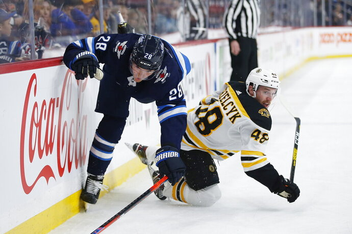 Winnipeg Jets' Jack Roslovic (28) gets checked by Boston Bruins' Matt Grzelcyk (48) during the second period of an NHL hockey game Friday, Jan. 31, 2020, in Winnipeg, Manitoba. (John Woods/The Canadian Press via AP)