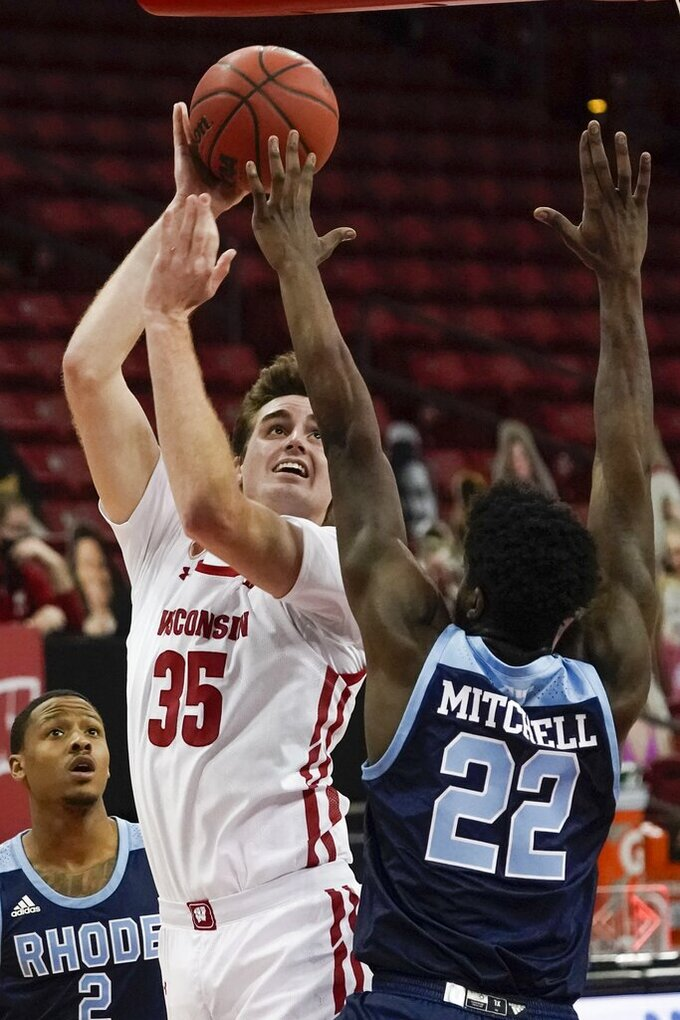 Wisconsin's Nate Reuvers shoots with Rhode Island's Makhel Mitchell defending during the first half of an NCAA college basketball game Wednesday, Dec. 9, 2020, in Madison, Wis. (AP Photo/Morry Gash)